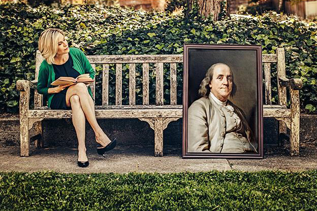 Stanford historian Caroline Winterer sits on a bench looking at a portrait of Ben Franklin