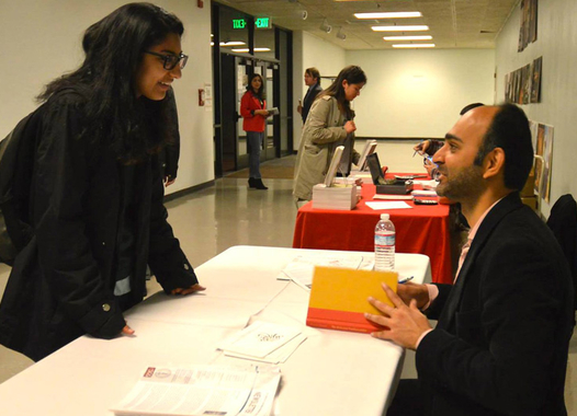 Photo of Mohsin Hamid signing a book for a guest