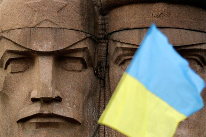 A Ukrainian flag partially obscures a monument to KGB officers in Kiev, Ukraine, Sunday.