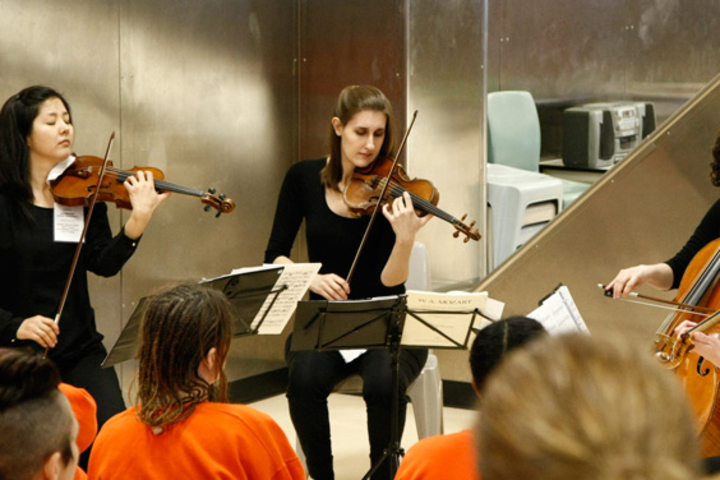 The Cecilia String Quartet performs for an audience of incarcerated women at the San Francisco County women's jail.