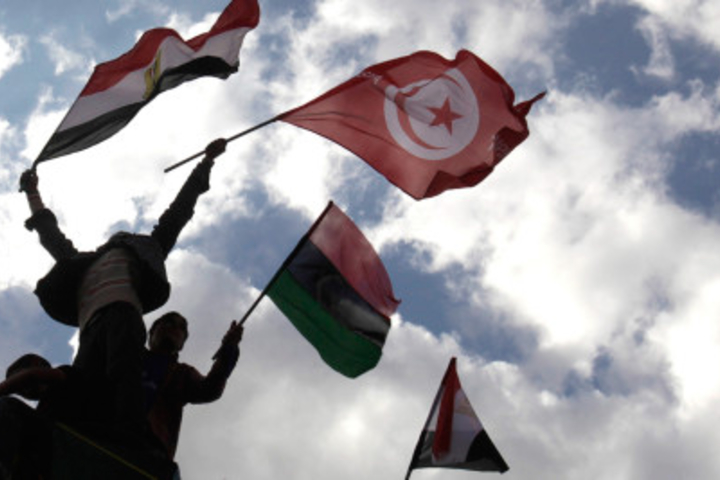 Protesters wave Egyptian, Libyan, and Tunisian flags during a protest in Cairo, Egypt's Tahrir Square on April 8, 2011.