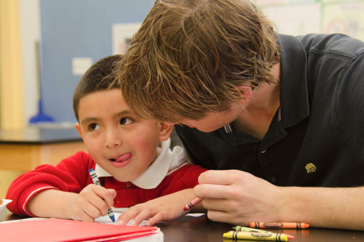 A Stanford student works with a boy at the Ravenswood Reads program sponsored by Haas Center for Public Service.
