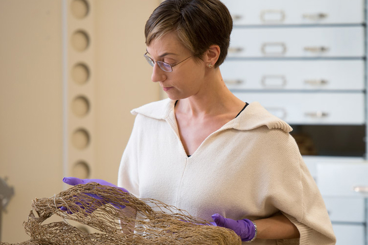 Christina Hodge, academic curator and collections manager for Stanford's Archaeology Collections, examines a late 19th-century dip net for salmon and eel from the Daggett Collection.