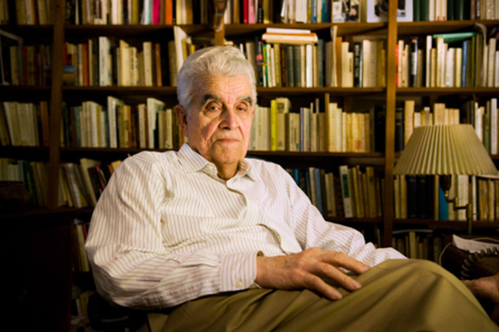 Girard sitting in chair in front of book shelf