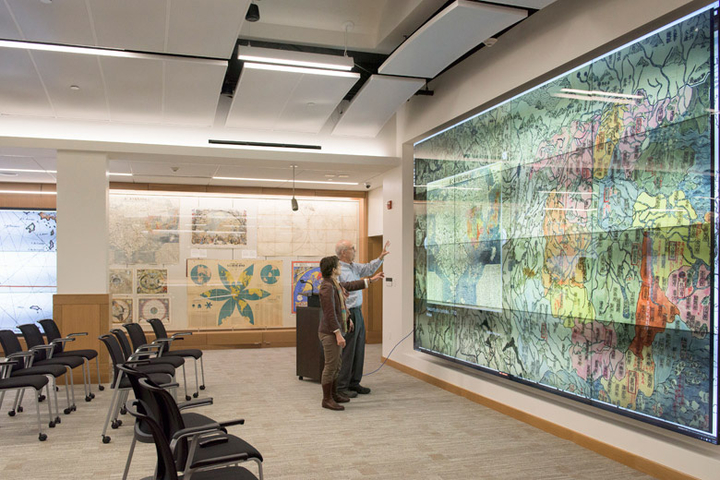 Exhibition designer Becky Fischbach talks with David Rumsey in the David Rumsey Map Center in Green Library.