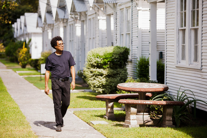 Artist Rick Lowe walking in front of row houses
