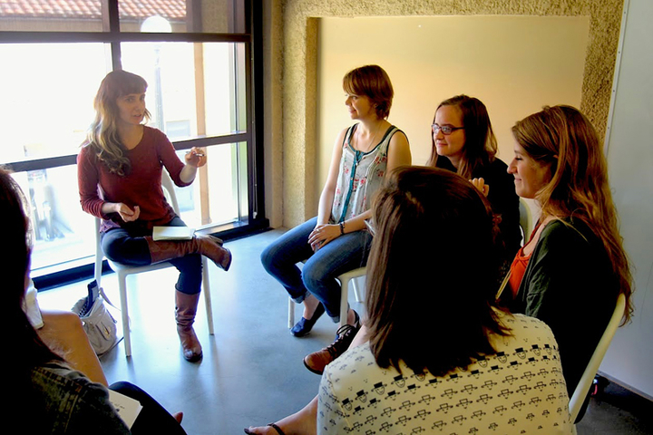 Students sitting in a circle talking.
